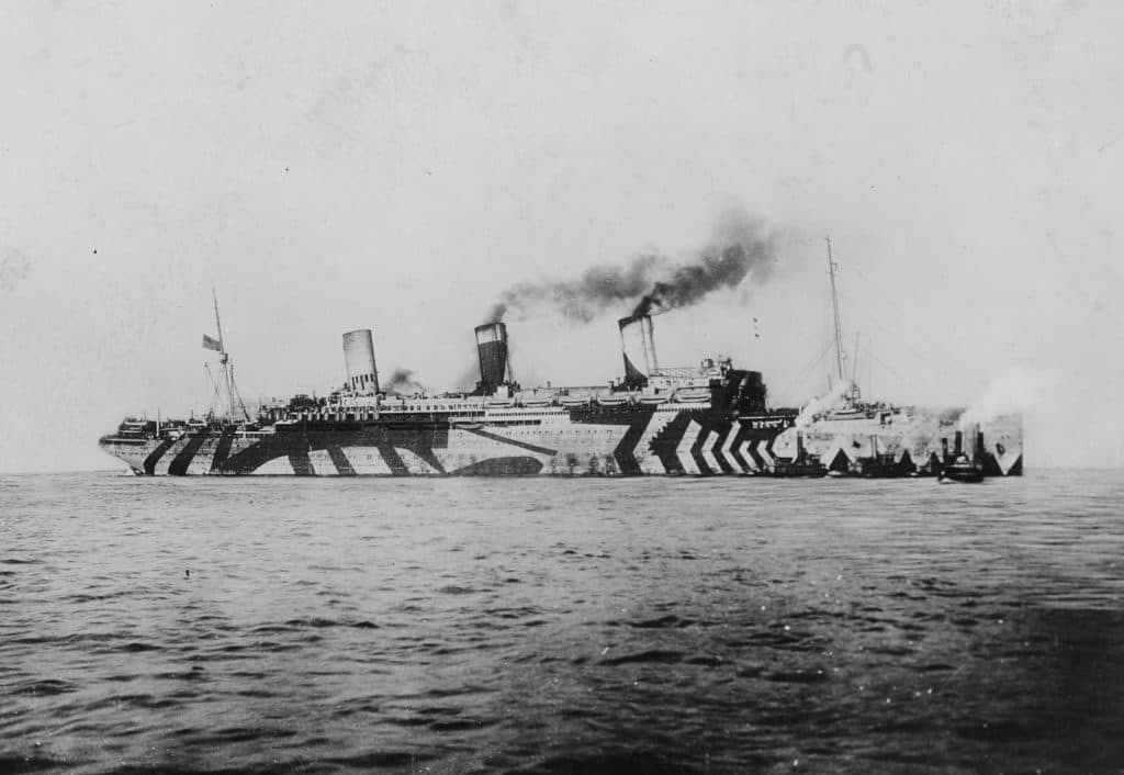 """USS Leviathan, formerly the Hamburg-Amerika liner Vaterland, in """"dazzle"""" camouflage. The Leviathan carried 96,804 American troops, among them the headquarters and one brigade of the 79th Division, to France. (U.S. Naval Historical Center)"""