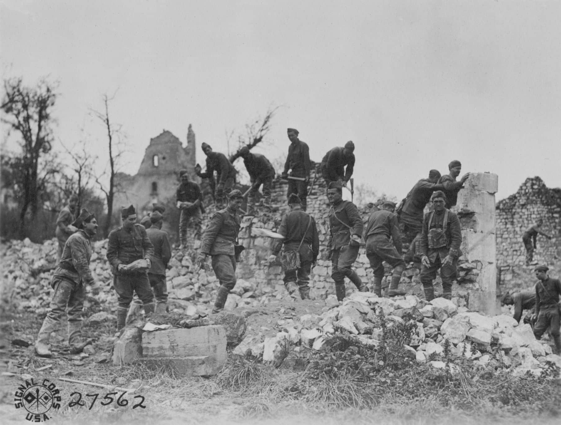 Men of the 304th Engineers tearing down walls of a ruined village behind the front.  The rocks would be used in repairing the roads. (AHEC)